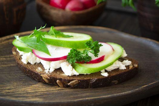 Bruschetta sandwiche with cucumbers, radishes and persil microgreen on wooden board
