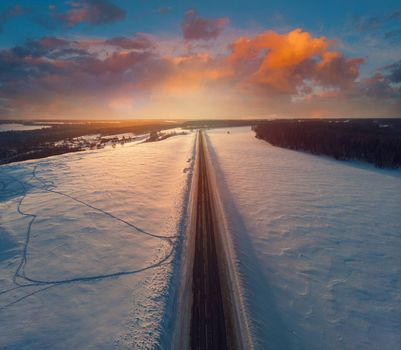 Aerial view of a road with sunset sky in winter landscape