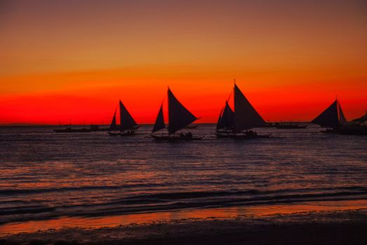Dramatic orange sea sunset with sailboats in tropical country, clouds. Wide angle. silhouettes of boats, the solar disk. Philippines, Boracay