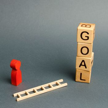 Blocks tower with word Goal and a man figurine with a fallen ladder. Tools and tactics objective achievement, puzzle solving. Finding solutions in a situation. Achieving success and solving a problem.