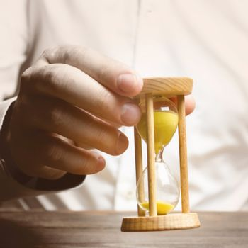 The person holds an hourglass in his hands. Business management. Logistics, process efficiency, savings. Time management. Awareness of time constraints. Pension, countdown, deadline. Self discipline