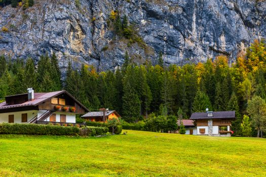 Autumn in the famous Dolomites mountains, Italy, Europe. Dramatic cliffs surround the village with the the iconic mountains and autumn forest. Colorful autumn landscape in mountain village.