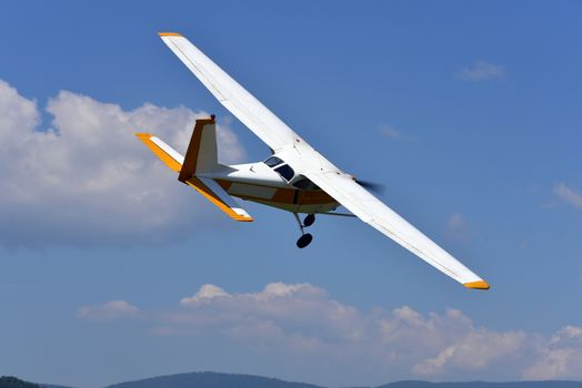 A small single engine aircraft flying in the blue sky