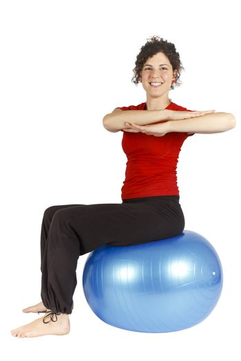 Smiling young woman sitting on a blue yoga ball doing an exercise.