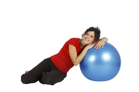 Young woman sitting with a blue yoga ball.