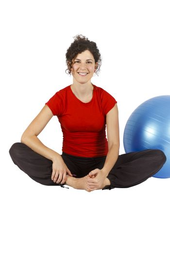 Young woman sitting with a blue yoga ball behind her.