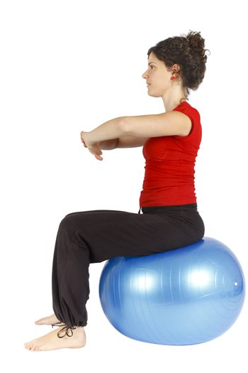 Young woman sitting on a blue yoga ball doing an exercise.