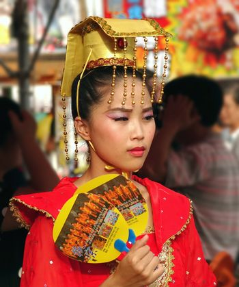 KAOHSIUNG, TAIWAN -- AUGUST 15, 2015: A beautiful female dancer with an elaborate headdress awaits her turn at the outdoor Third Prince temple carnival.