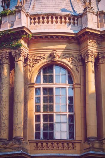Arched window with a beautiful ancient stone relief ornamental decoration, portrait, floral elements and pillars. Vajdahunyad Castle in the City Park of Budapest, Hungary, Europe. Old decorative European facade detail.