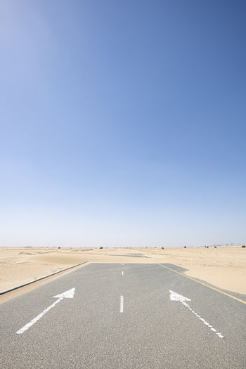 Vertical shot of an empty road covered by sand in the desert with large copy space in the blue sky