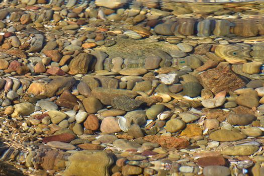 Distorted rocks, pebbles and shells in a natural coastal water pool, Mossel Bay, South Africa