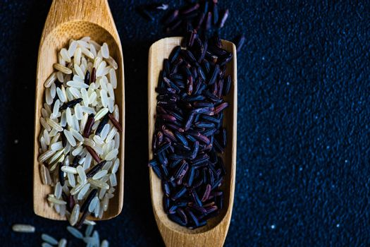 Organic black and wild rice in wooden spoons  as a cooking ingredients on concrete background with copy space