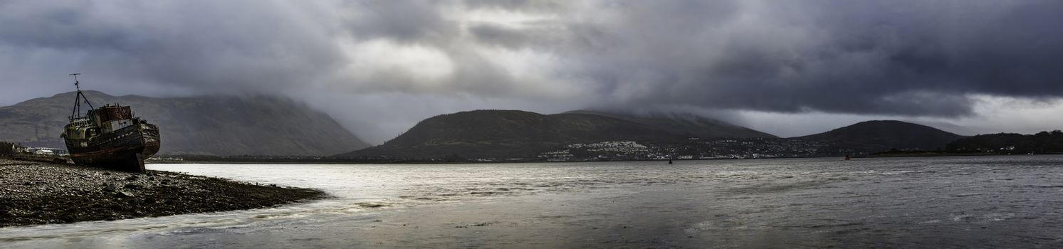 Glencoe, Scotland - Jan 2020: Panorama of moody skies hanging over the boat wreck of the Corpach, with Ben Nevis and Fort William behind.