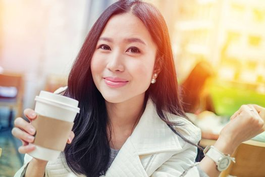 Woman drinking coffee at restaurant with sunrise streaming