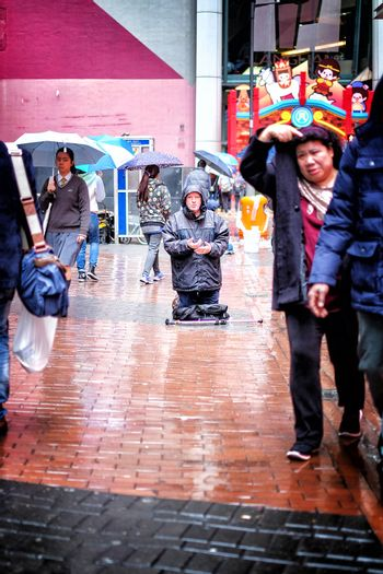 Hong Kong January 15 2016 : People passing a homeless man praying on the street on the rainy day in Hong Kong city in 15 Jan 2016