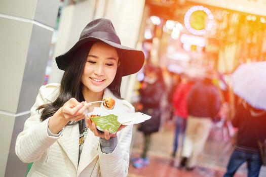 Chinese Asian young female model eating dumpling batter (Takoyaki) on Street in Hong Kong