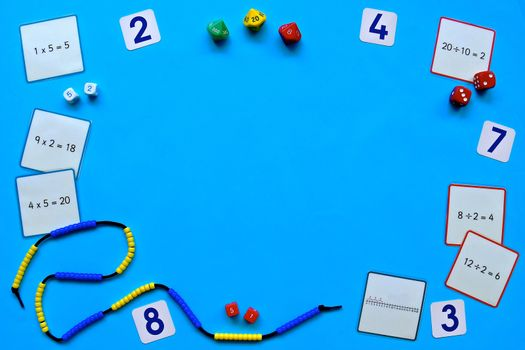 Maths concept flatlay on a blue background with copyspace, focusing on number, addition, subtraction and counting with beaded number lines, place value dice and problem task cards.