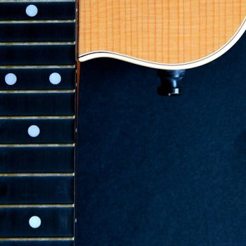 Partial aerial view of the neck and body of a wooden acoustic guitar isolated on a black background.