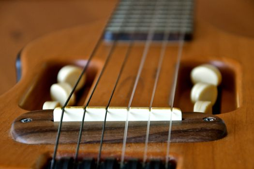 Close up view of the bridge and strings on a mandolin.