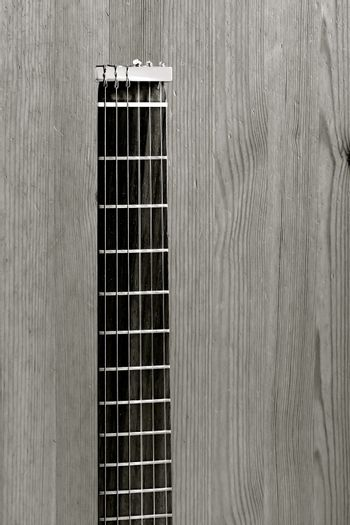 Black and white aerial view of the neck of a travel guitar on a rustic wooden background.