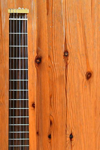 Aerial view of a the neck of a travel guitar on a rustic wooden background.