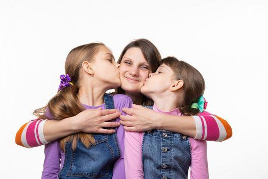 Children joyfully kiss mom, isolated on white background