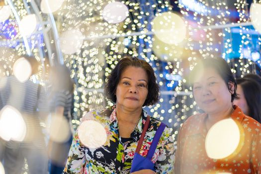 Asian women 60s and 40s plump body fashion happy for relax in night time with bokeh of light decoration for happy new year celebration