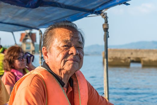 Asian elderly man sailing on Songkaria river by long tail boat with sun light in evening time when vacation travel for relax
