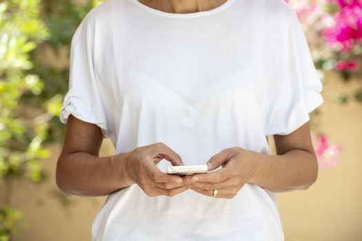 Woman in the forty's using a smartphone with white t-shirt for background or presentation, with large copy space and flowers background