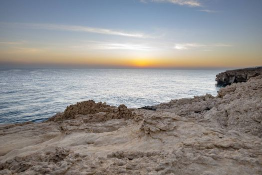 Sunset over the sea and the wild coast of the Sultanate of Oman