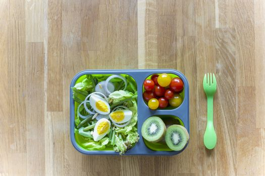 Collapsible silicon lunch box with food (green salads, eggs, tomatoes, kiwi) on wooden table
