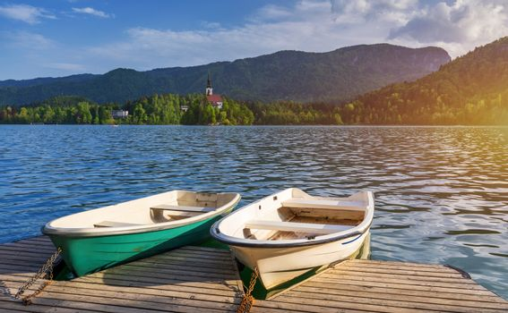 Iconic Bled scenery. Boats at lake Bled, Slovenia, Europe. Wooden boats with Pilgrimage Church of the Assumption of Maria on the Island on Lake Bled, Slovenia
