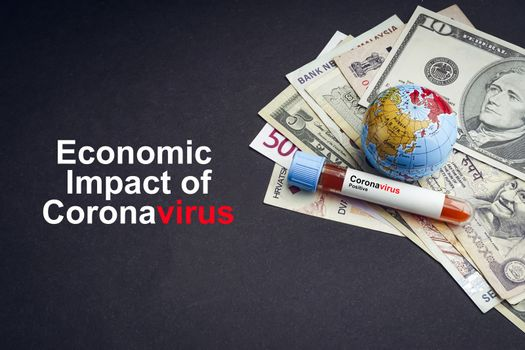 ECONOMIC IMPACT OF CORONAVIRUS text with currency banknotes, world globe and blood test vacuum tube on black background. Covid-19 or Coronavirus Concept