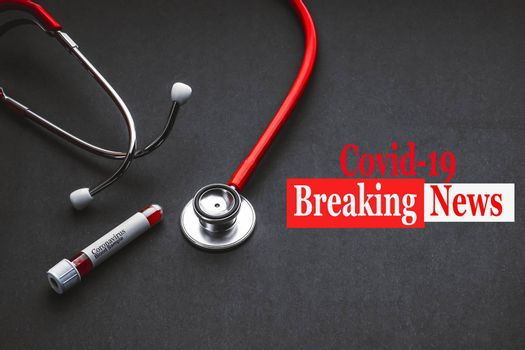 COVID-19 BREAKING NEWS text with stethoscope and blood sample vacuum tube on black background. Covid or Coronavirus Concept