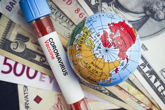 CORONAVIRUS VACCINE text with currency banknotes, world globe and blood test vacuum tube on black background. Covid-19 or Coronavirus Concept