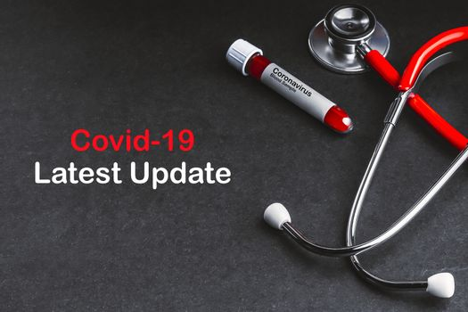 COVID-19 LATEST UPDATE text with stethoscope and blood sample vacuum tube on black background. Covid or Coronavirus Concept