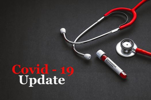 COVID-19 UPDATE text with stethoscope and blood sample vacuum tube on black background. Covid or Coronavirus Concept