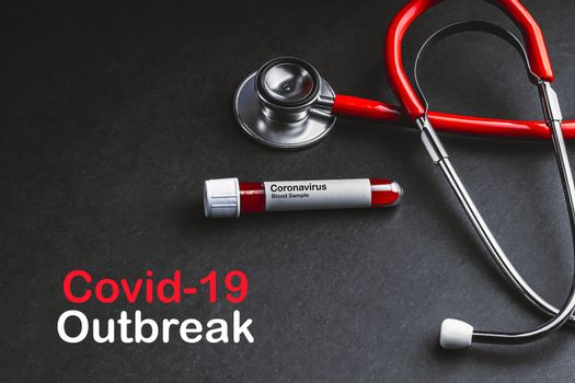 COVID-19 OUTBREAK  text with stethoscope and blood sample vacuum tube on black background. Covid or Coronavirus Concept