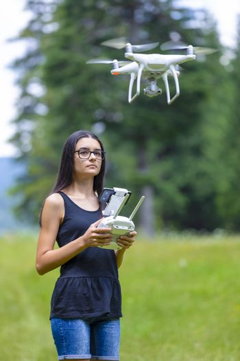 Teenage girl controlling drone with remote control and having fun in summer time.  Focus on her face.