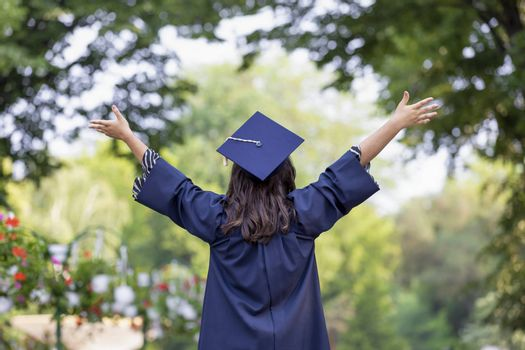 Back view of young woman graduating put her hands up and celebrating feeling so happy.