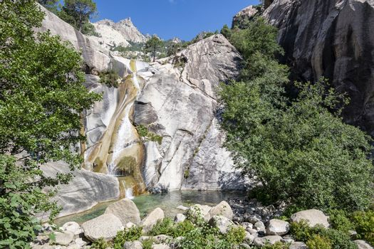 Waterfall and natural pool in the famous Purcaraccia Canyon in Bavella during summer, a tourist destination and attraction (for canyoning and hiking). Corsica, France