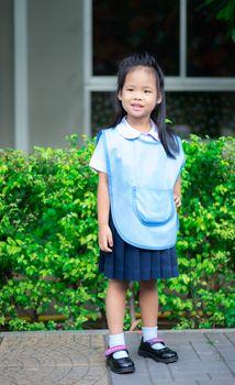 Portrait of happy little girl in Thai school uniform standing on footpath, ready back to school