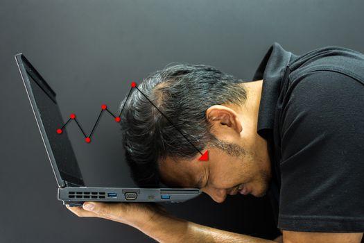 Asian man 40s and computer stock market graph fall