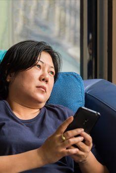Asia women 40s holding smartphone thinking on sofa