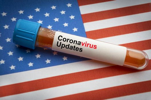 CORONAVIRUS COVID-19 UPDATE text and blood sample vacuum tube on America flags background. Covid-19 or Coronavirus Concept