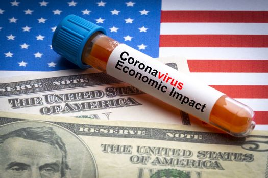 CORONAVIRUS ECONOMIC IMPACT text, US Dollar and blood sample vacuum tube on America flags background. Covid-19 or Coronavirus Concept