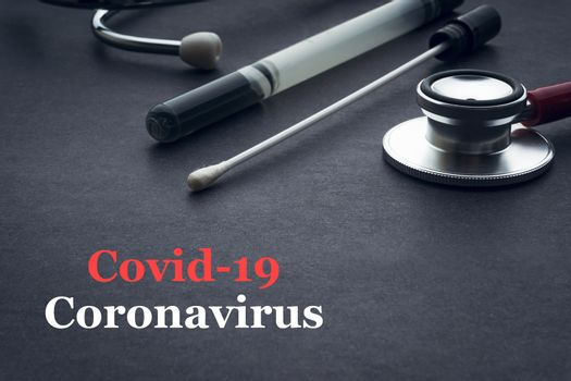 COVID-19 or CORONAVIRUS text with stethoscope and medical swab on black background. Covid-19 or Coronavirus concept.