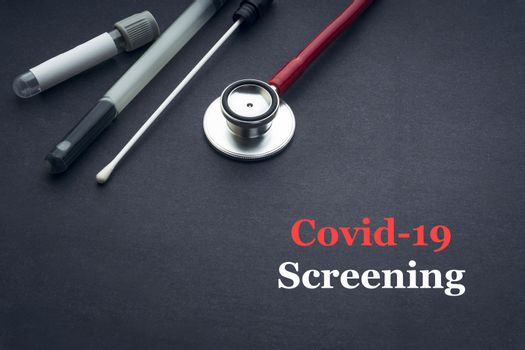 COVID-19 or CORONAVIRUS SCREENING text with stethoscope, medical swab and blood sample tube on black background. Covid-19 or Coronavirus concept.