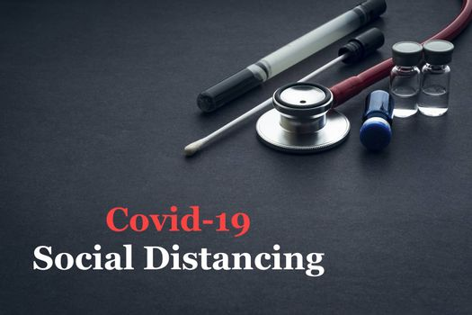 COVID-19 or CORONAVIRUS SOCIAL DISTANCING text with stethoscope, medical swab and vial on black background. Covid-19 or Coronavirus concept.