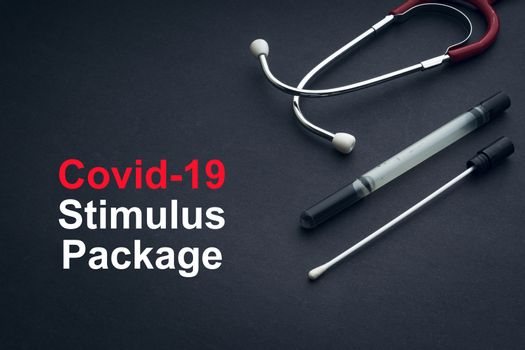 COVID-19 or CORONAVIRUS STIMULUS PACKAGE text with stethoscope and medical swab on black background. Covid-19 or Coronavirus concept.